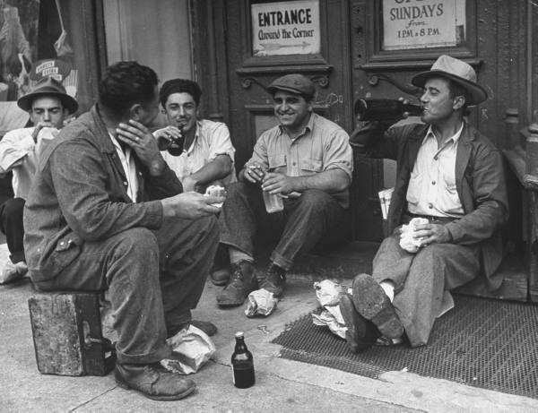 men-sitting-on-street-drinking-from-bottles-during-lunch-break